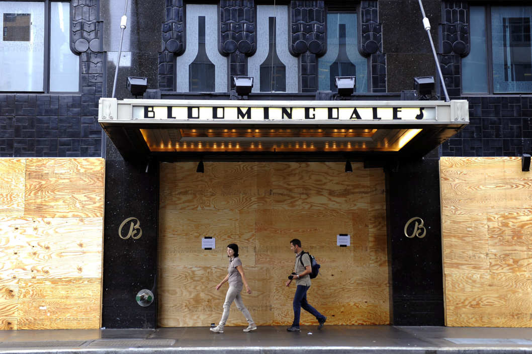 Tourists walk past a boarded up  Bloomingdales store in New York  August 28, 2011 soon after Hurricane Irene passed through the city with rain and high winds. AFP PHOTO / TIMOTHY A. CLARY (Photo credit should read TIMOTHY A. CLARY/AFP/Getty Images)