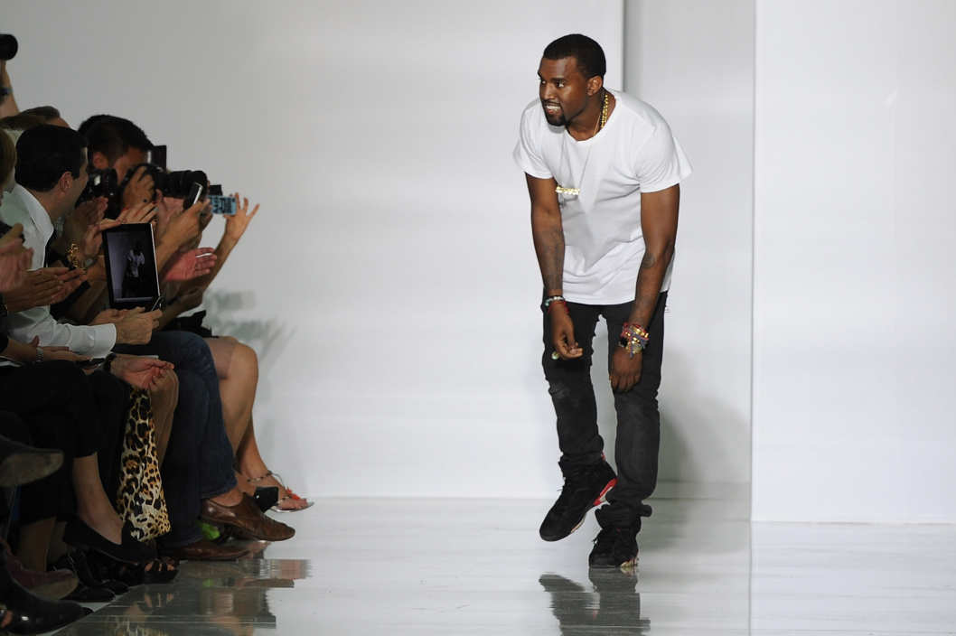 PARIS, FRANCE - OCTOBER 01:  Kanye West acknowledges the applause of the audience after the Dw by Kanye West Ready to Wear Spring / Summer 2012 show during Paris Fashion Week at Lycee Henri IV on October 1, 2011 in Paris, France.  (Photo by Pascal Le Segretain/Getty Images)