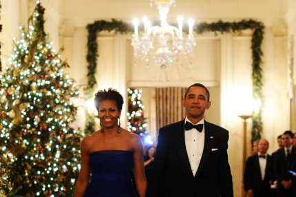 US President Barack Obama and First Lady Michelle Obama arrive in the East Room of the White House to attend a reception for Kennedy Center Honorees in Washington, DC, on December 4, 2011.