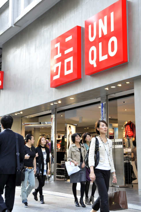 Shoppers walk past a branch of Japanese clothes retailer Uniqlo in Tokyo