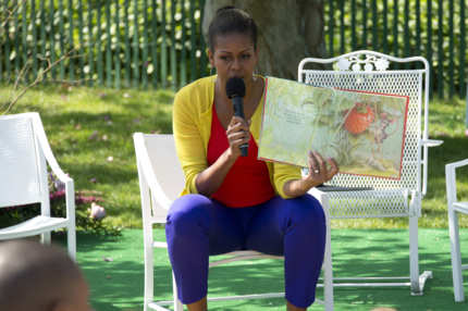 First Lady Michelle Obama reads a book to children during the 2012 White House Easter Egg Roll