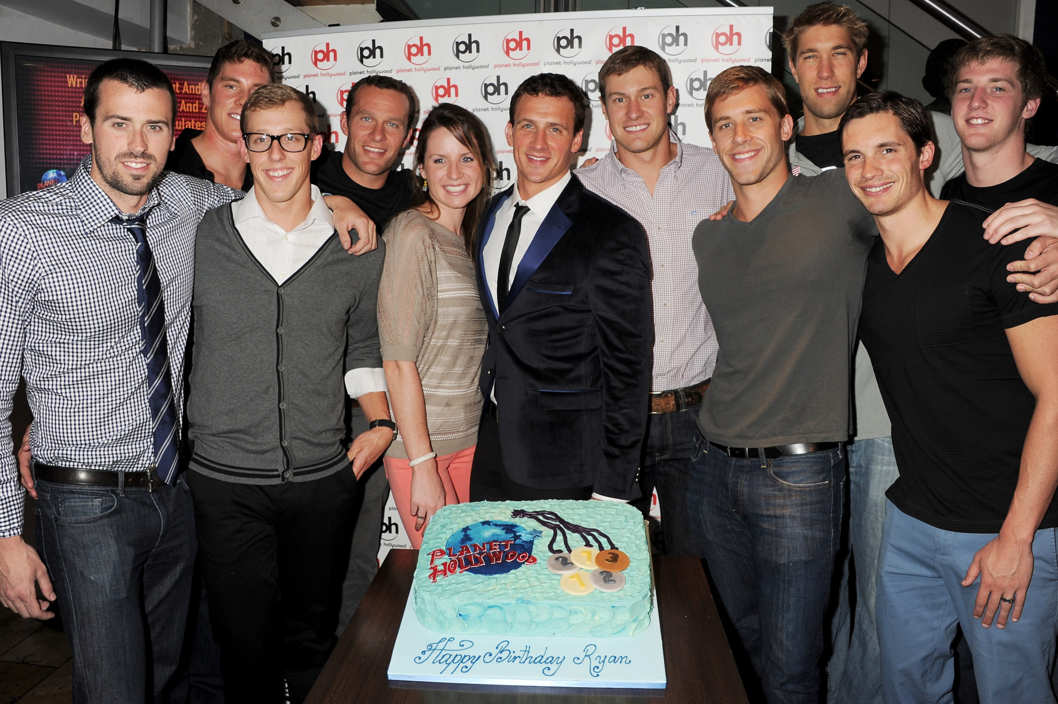 U.S. Olympic Swimmer Ryan Lochte (C) celebrates his 28th birthday with U.S. Olympic Swim Team members (L to R) Davis Tarwater, Conor Dwyer, Tyler McGill, Brendan Hansen, Kara Lynn Joyce, Peter Vanderkaay, Nick Thoman, Matthew Grevers, Eric Shanteau and Jimmy Feigen at Planet Hollywood on August 7, 2012 in London, England.