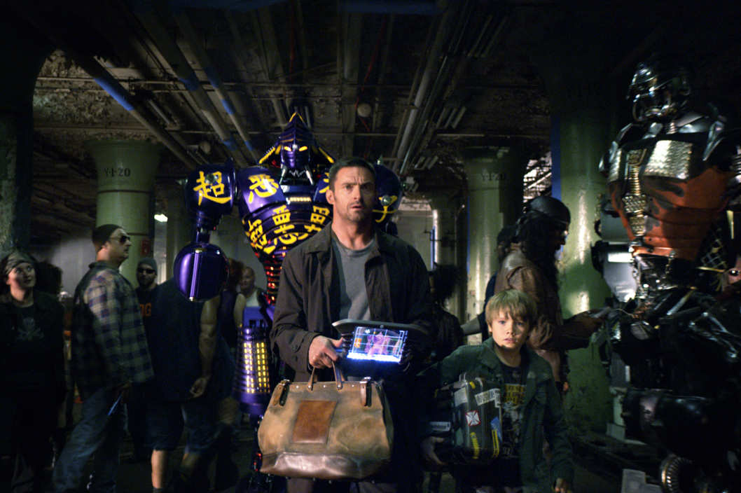 """REAL STEEL""  RS-FF-006  Down-on-his-luck fight promoter Charlie Kenton (Hugh Jackman, left) and his son, Max (Dakota Goyo, right) enter their star robot boxer Noisy Boy in a match at the Crash Palace in DreamWorks Pictures' action drama ""Real Steel"".  ?DreamWorks II Distribution Co., LLC. ?All Rights Reserved."