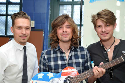 NEW YORK - OCTOBER 22:  (L-R) Zac Hanson, Taylor Hanson, and Isaac Hanson of the band Hanson hold a guitar painted by the band during the VH1 Save the Music Foundation Family Day at the The Anderson School on October 22, 2011 in New York City.  (Photo by Mike Coppola/Getty Images)