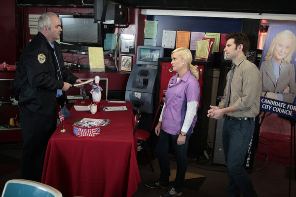 "PARKS AND RECREATION -- ""Bowling for Votes"" Episode 413 -- Pictured: (l-r) Will McLaughlin as officer, Amy Poehler as Leslie Knope, Adam Scott as Ben Wyatt."
