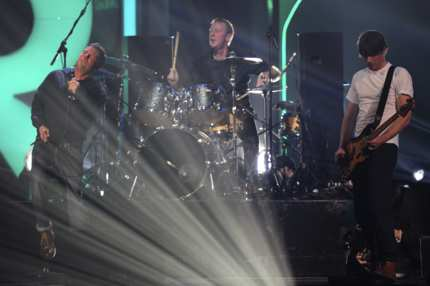 Damon Albarn (L) sings with drummer Dave Rowntree (C) and bassist Alex James (r) as the British alternative rock band Blur perform live on stage at the end of the BRIT Awards 2012 in London on February 21, 2012.