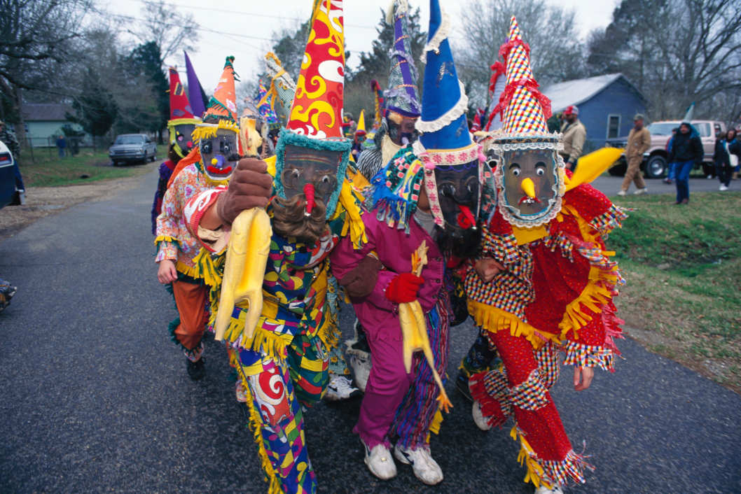 "February 1997, Louisiana, USA --- Original caption: Louisiana: Each year at Mardi Gras time, rowdy parades roll and revelers fight over worthless trinkets, an equally crazed celebration unfolds in the Cajun and Creole country 150 miles to the west. Hundreds of horseback riders dressed in medieval mummers costumes and masks gather for the purpose of chasing chickens. This is rural Mardi Gras, a pre-Lenten celebration from medieval Europe. As they have for generations for four days before Ash Wednesday, the celebrant go about collecting ingredients for a group gumbo, seeking ""charity"" - a dominion of rice, sausage, onions - or a chicken. If a chicken is offered it is not simply handed over, but tossed into flight and then frantically followed over fences, through fields and streams until it is caught by hand. While the poultry is being pursued, the other costumed characters dance, gulp beer and generally cut up. The --- Image by ? Mark Peterson/Corbis"
