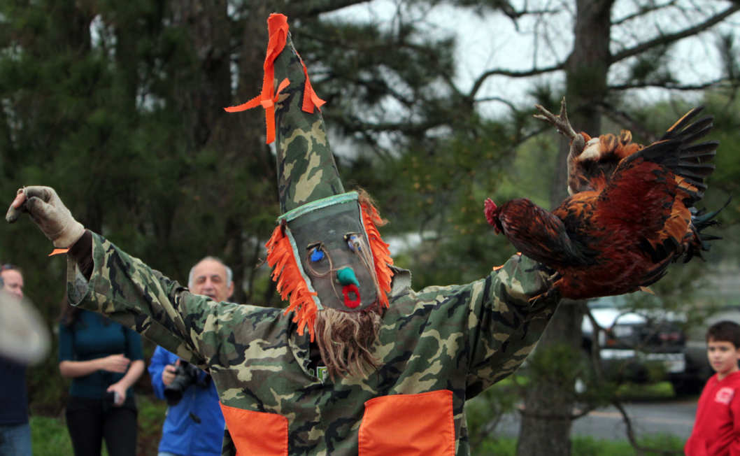 A costumed courir participant, known as a Mardi Gras, holds up a chicken after chasing and catching it during the Tee Mamou-Iota Courir de Mardi Gras in rural Acadia Parish near Iota, La., Tuesday morning March 8, 2011. (AP Photo/The Daily Advertiser, Leslie Westbrook)