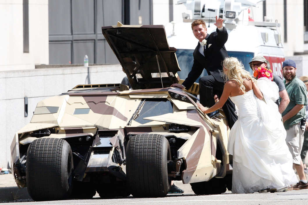 "PITTSBURGH, PA  - JULY 30:  A newly married couple waves to the crowd after being allowed to view the Tumbler after their wedding at a church across the street from the set of ""The Dark Knight Rises"" filming near the Carnegie Mellon University Software Engineering Institute Building in the neighborhood of Oakland on July 30, 2011 in Pittsburgh, Pennsylvania. (Photo by Jared Wickerham/Getty Images)"